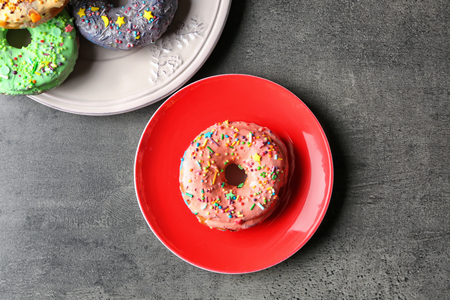 Plates with yummy colorful donuts on grey background