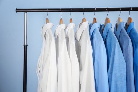 Clean shirts hanging on rack in laundry Banque d'images