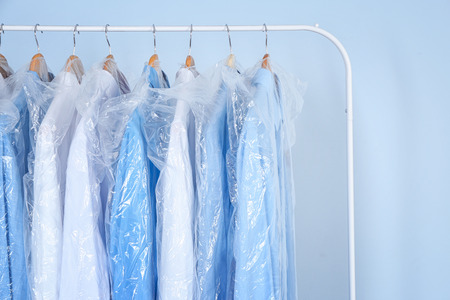 Clean shirts hanging on rack in laundry 写真素材