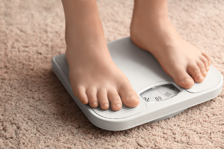 Overweight boy using scales at home Stockfoto