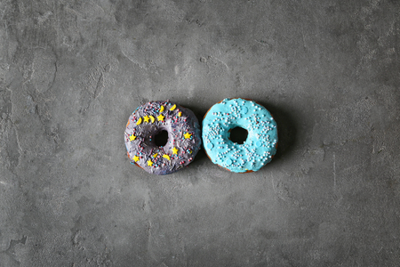 Fresh yummy colorful donuts on grey background