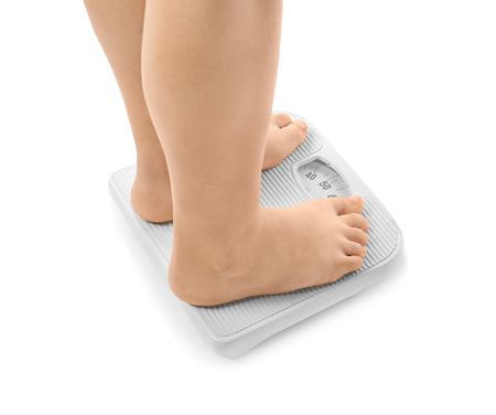 Legs of overweight boy using scales on white background