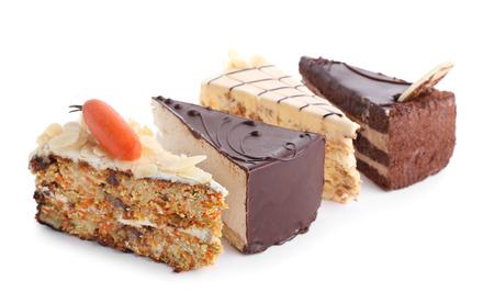 Trozos de sabrosos pasteles sobre fondo blanco. Foto de archivo