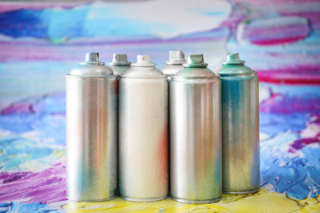 Aluminum aerosol cans with paints against blurred background