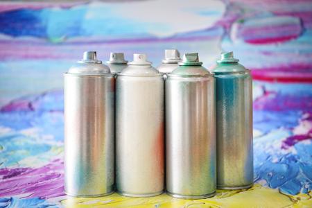 Latas de aerosol de aluminio con pinturas contra el fondo borroso