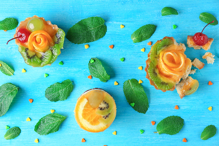 Composition with tasty fruit cakes on wooden background Imagens