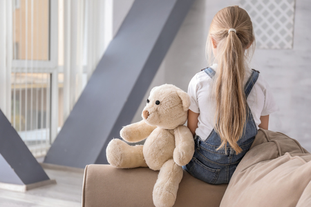 Lonely little girl with teddy bear in room. Autism concept