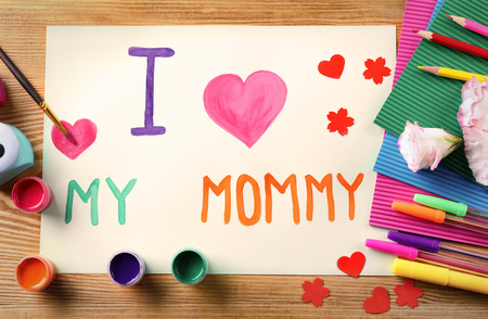 Cute handmade card with text I LOVE MY MOMMY on wooden table. Mother's day celebration
