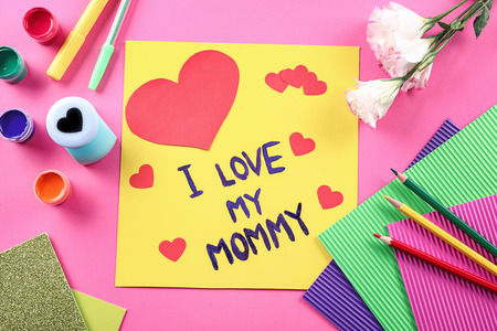 Cute handmade card with text I LOVE MY MOMMY on table. Mother's day celebration Banco de Imagens