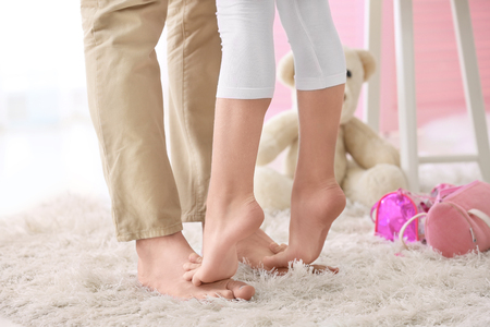 Cute little girl standing on father's feet at home