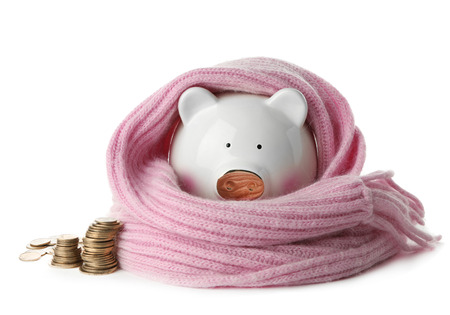 Piggy bank with warm scarf and coins on white background Imagens