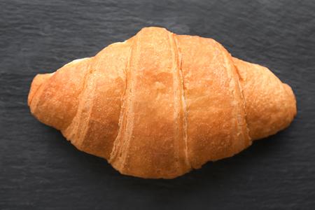 Fresh yummy croissant on dark background