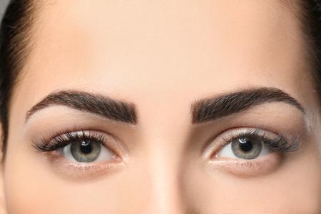 Młoda kobieta z permanentnym makijażem brwi, zbliżenie