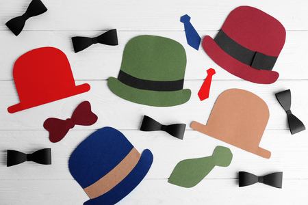 Paper hats and bow ties on light wooden background. Father's Day composition Banco de Imagens