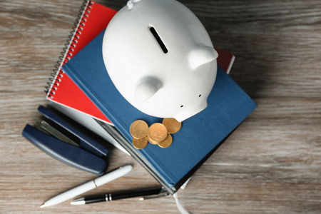 Piggy bank with stack of notebooks on wooden background