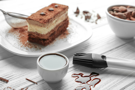 Chocolate syrup and tasty cake on wooden table
