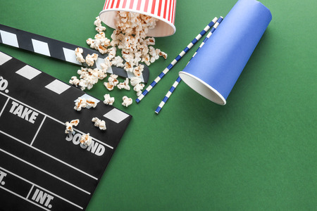Composition with popcorn and movie clapper on color background