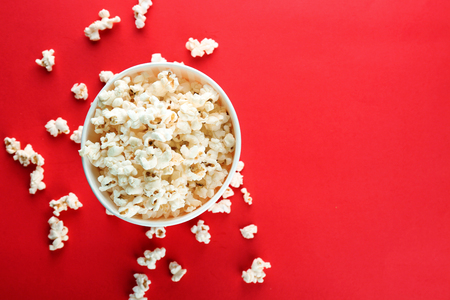 Cup with popcorn on color background