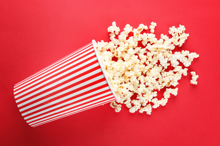 Cup with popcorn on color background Banco de Imagens