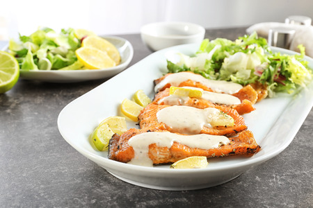 Tasty rainbow trout fillets with sauce on plate, closeup Stockfoto