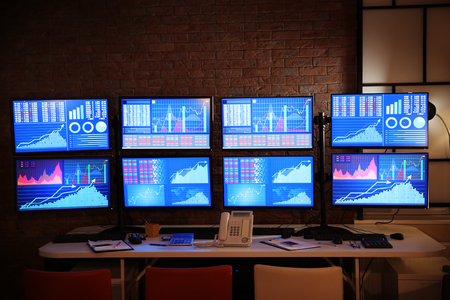 Modern stock trader's workplace in office at night Foto de archivo