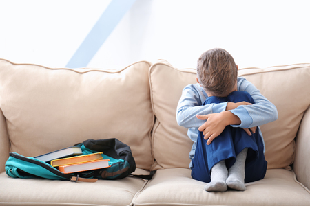 Depressed little boy on couch at home