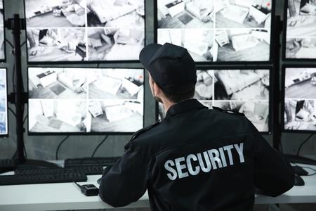 Mannelijke bewaker die in de bewakingsruimte werkt Stockfoto