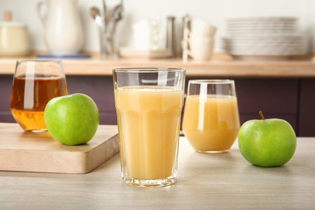 Glass of delicious apple juice on kitchen table