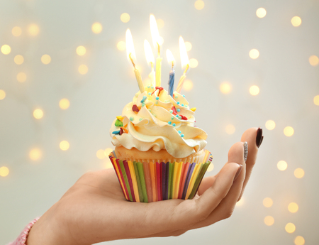 Woman holding birthday cupcake with candles against blurred lights, closeup