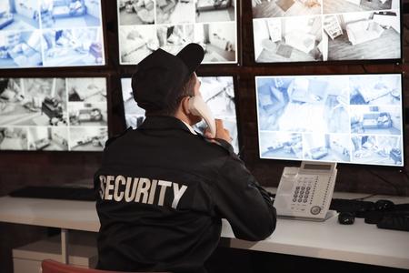 Guardia de seguridad masculino hablando por teléfono en la sala de vigilancia
