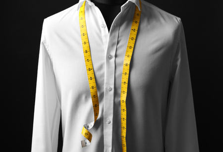 Elegant custom made shirt on mannequin against black background, closeup