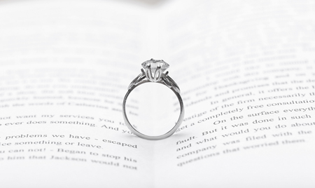 Engagement ring between pages of book, closeup Banco de Imagens