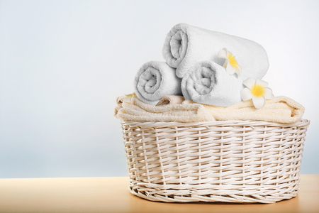 Wicker basket with clean towels on table against light background