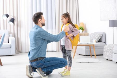 Giovane che aiuta sua figlia a prepararsi per la scuola