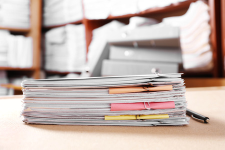 Stack of old paper documents on table in archive