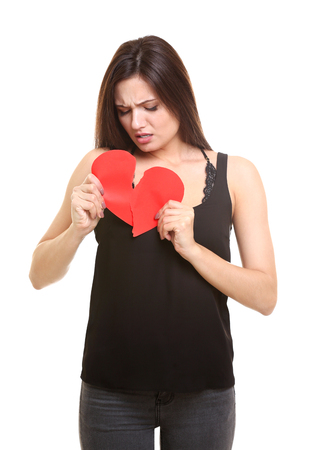 Young woman holding torn paper heart on white background