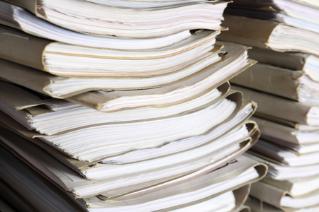 Stack of old folders with documents in archive, closeup