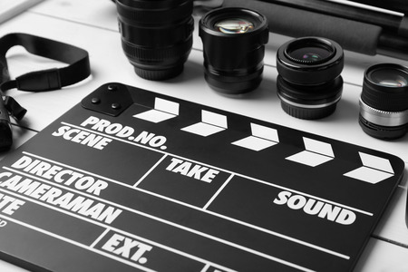Movie clapper and lenses on light background, closeup