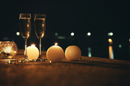 Romantic composition with burning candles and glasses of champagne at night, outdoors