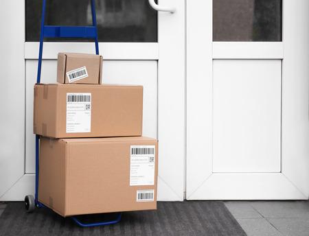 Postal cart with delivered parcels near front door Banco de Imagens