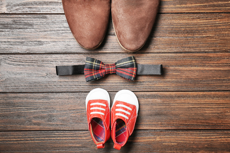 Bow tie, big and small shoes on wooden background. Father's day composition Banque d'images