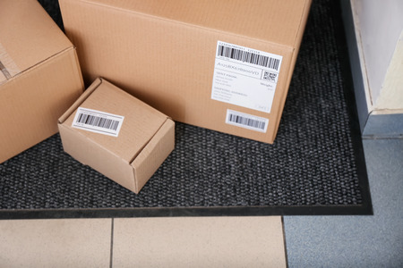 Delivered parcels on doormat, closeup Imagens