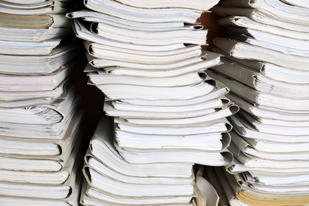 Stacks of old folders with documents in archive