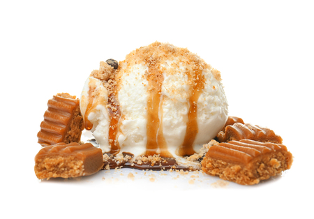 Ice cream ball with caramel sauce and candies on white background