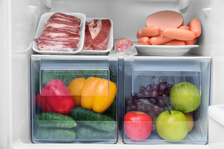 Meat products, fruit and vegetables in refrigerator, closeup