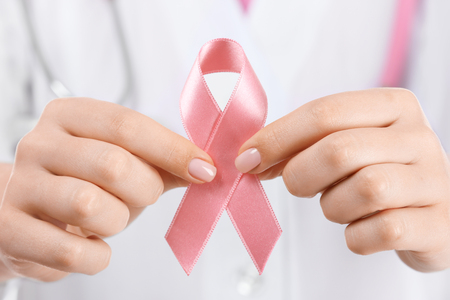 Doctor holding pink ribbon, closeup. Breast cancer awareness concept