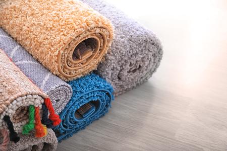Coloridas alfombras enrolladas en el suelo
