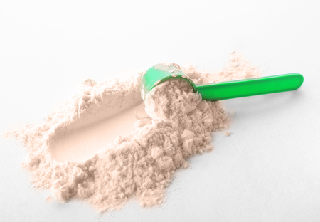 Measuring scoop and protein powder on white background