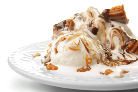 Plate with ice cream and caramel sauce on white background