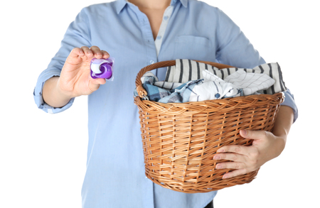 Woman holding basket with laundry and detergent on white background